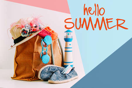 Summer holiday travel concept.Hipster Beach bag with items for a day at the seaside on colorful with hello summer word background