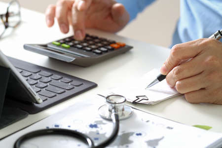 의료 비용 및 수수료 개념. 현대 병원에서 의료 비용에 대 한 계산기를 사용하는 스마트 의사의 손에