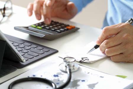 Gezondheidszorgkosten en prijzenconcept. Hand van slimme arts gebruikte een calculator voor medische kosten in het moderne ziekenhuis