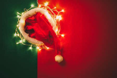 Groeten seizoen concept.Santa Claus hoed met Kerstmis licht op rode en groene achtergrond