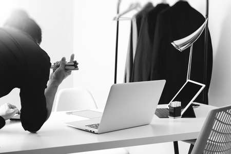 Fashion designer working with mobile phone and using laptop with digital tablet computer in modern studio,black and white Stock Photo