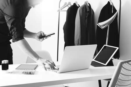 work: Fashion designer working with mobile phone and using laptop with digital tablet computer in modern studio,black and white Stock Photo