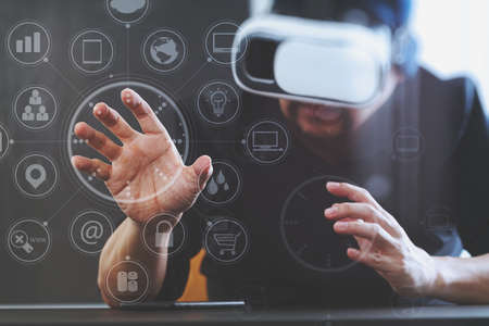 Zakenman draagt virtuele realiteit bril in modern kantoor met mobiele telefoon met behulp van VR-headset met scherm icoon diagram