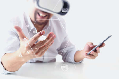 simulation: businessman wearing virtual reality goggles in modern office with mobile phone using with VR headset with screen icon diagram