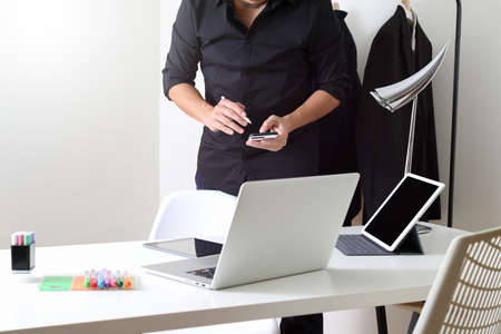 stylus pen: Fashion designer working with mobile phone and using laptop with digital tablet computer in modern studio