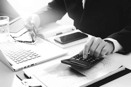zakenman hand werken met de financiën over kosten en rekenmachine en latop met mobiele telefoon op met bureau in moderne kantoor, zwart en wit