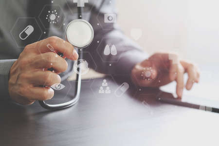 researching: close up of smart medical doctor working with stethoscope and mobile phone on dark wooden desk in modern hospital with virtual reality icon diagram