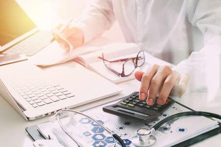 Gesundheitswesen Kosten und Gebühren concept.Hand von smart Arzt verwendet einen Taschenrechner für medizinische Kosten in modernen Krankenhaus
