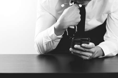 researching: close up of businessman working with smart phone on wooden desk in modern office,black and white