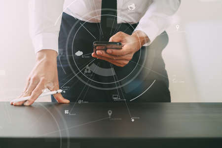 close up of businessman working with smart phone on wooden desk in modern office with virtual icon diagram Stock Photo