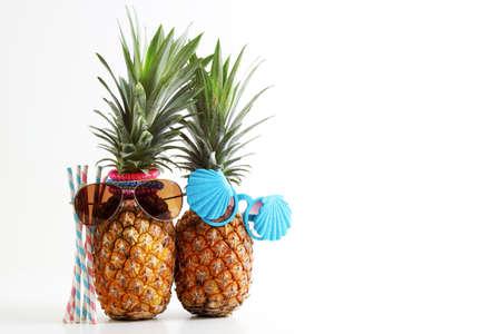 新婚旅行や休日のコンセプトです。白い背景のスタイリッシュなサングラスでは魅力的なパイナップルのカップル