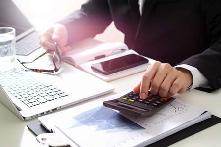 Zakenman hand werken met financiën over kosten en rekenmachine en latop met mobiele telefoon op withe bureau in moderne kantoor Stockfoto