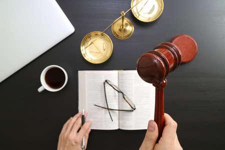 Concetto di giustizia e di legge. Vista su una mano di giudice maschio in una sala di tribunale con la scala di ottone e ottone e computer e libro di bibbia aperto su tavola di legno scuro Archivio Fotografico - 81629636