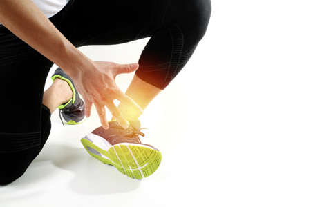 スポーツ傷害と白い背景に捻挫するため足に触れるアスレチック男ランナー スポーツマン足首痛みでツイスト ブロークンで共同開催を実行します。 写真素材