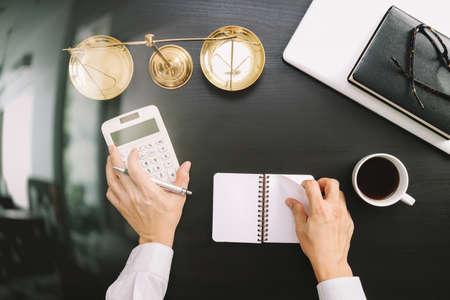 rechtvaardigheid en recht concept.businessman of advocaat of accountant werken aan rekeningen met behulp van een rekenmachine en een laptop computer en documenten in moderne kantoor