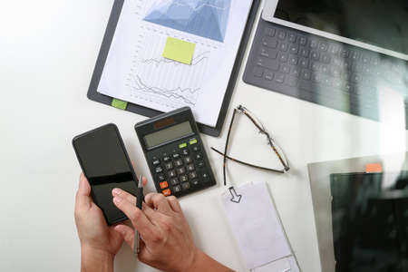 working office: top view of businessman hand working with finances about cost and calculator and latop with mobile phone on withe desk in modern office Stock Photo