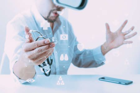 smart doctor wearing virtual reality goggles in modern office with mobile phone using with VR headset with screen icon diagram Stock Photo