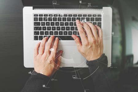 가상 현실 아이콘 다이어그램과 함께 현대 사무실에서 나무 책상에 노트북 컴퓨터와 키보드를 입력하는 사업가의 상위 뷰