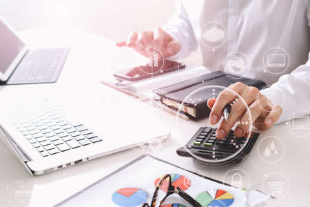 businessman hand working with finances about cost and calculator  and latop with mobile phone on withe desk in modern office with VR icon diagram