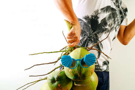 blue green background: Summer and holiday fashion concept.Man Wearing palm trees graphics on T-shirt and holding cluster of coconuts with items on white background Stock Photo