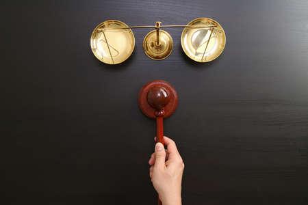 Le concept de la justice et de la loi.La vue du juge masculin maintient une salle d'audience avec le marteau et l'échelle en laiton sur la table en bois sombre Banque d'images - 81650807