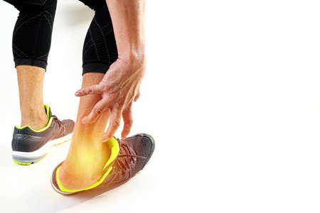 Corredor deportista sosteniendo el tobillo en el dolor con roto torcido conjunta correr lesión deportiva y atlético hombre tocando el pie debido a esguince sobre fondo blanco