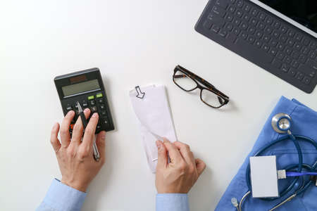 health care provider: top view of Healthcare costs and fees concept.Hand of smart doctor used a calculator for medical costs in modern hospital