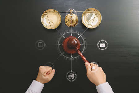 justice and law concept.Top view of Male judge hand in a courtroom with the gavel and brass scale on dark wood table with Vr diagram Stock Photo