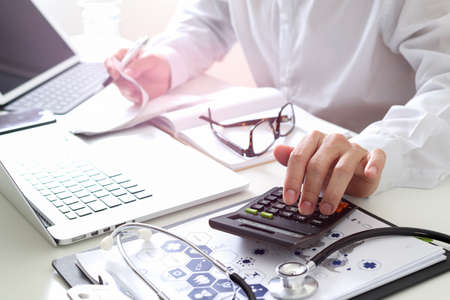 Concept de frais et honoraires de soins de santé. Main de docteur intelligent a utilisé une calculatrice pour les frais médicaux dans l'hôpital moderne Banque d'images - 81651086