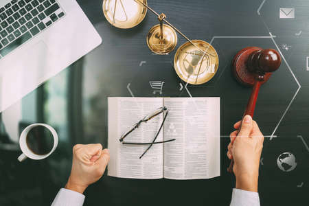 justice and law concept.Top view of Male judge hand in a courtroom with the gavel and brass scale and computer and open bible book on dark wood table with Vr diagram Stock Photo