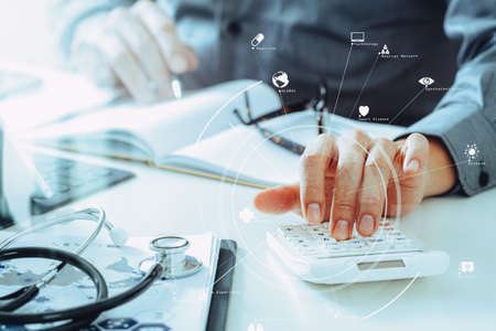Healthcare costs and fees concept.Hand of smart doctor used a calculator for medical costs in modern hospital with VR icon diagram Stockfoto