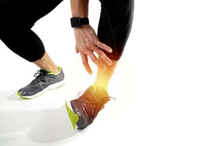 Esportista de corredor segurando o tornozelo com dor com lesão de esporte de articulação torcida quebrada e homem atlético tocando o pé devido a entorse no fundo branco Foto de archivo - 81651099