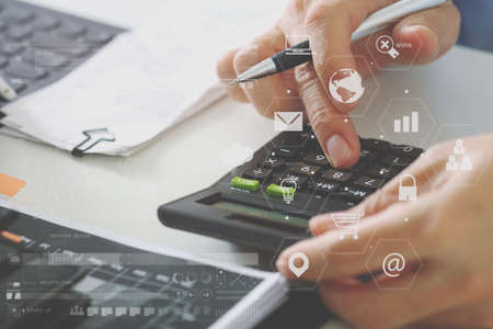 working office: close up of businessman hand working with finances about cost and calculator and latop with mobile phone on withe desk in modern office with VR icon diagram Stock Photo