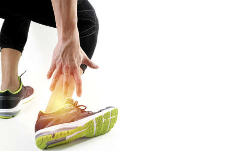 Runner sportsman holding ankle in pain with Broken twisted joint running sport injury and Athletic man touching foot due to sprain on white background Reklamní fotografie