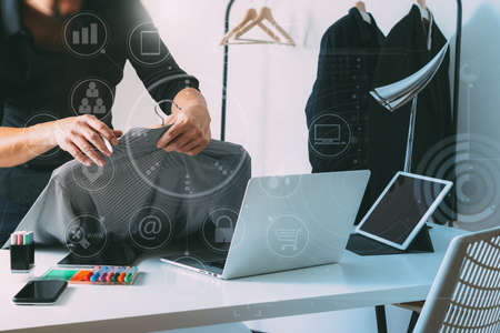 Fashion designer holding shirt and using laptop with digital tablet computer in modern studio with VR icon diagram