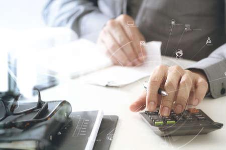 Zakenmanhand die met financiën over kosten en calculator en laptop met mobiele telefoon aan met bureau in modern bureau met VR-pictogramdiagram werken