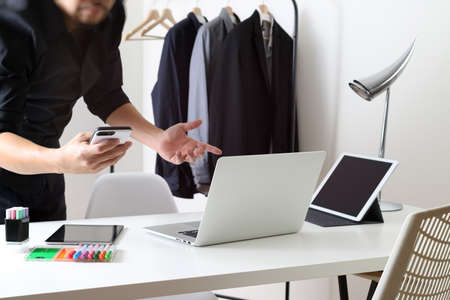 stylus pen: Fashion designer talking mobile phone and using laptop with digital tablet computer in modern studio Stock Photo