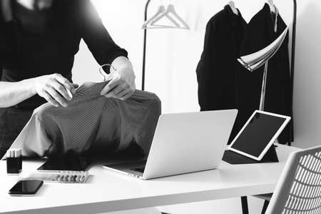 Fashion designer holding shirt and using laptop with digital tablet computer in modern studio ,black and white Stock Photo