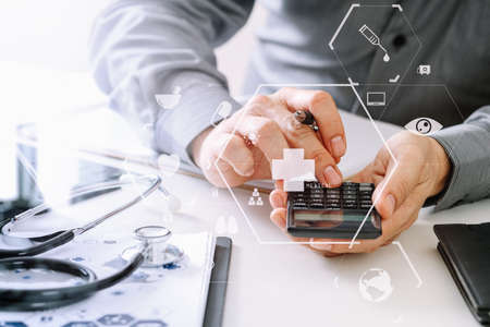 Healthcare costs and fees concept.Hand of smart doctor used a calculator for medical costs in modern hospital with VR icon diagram Stok Fotoğraf