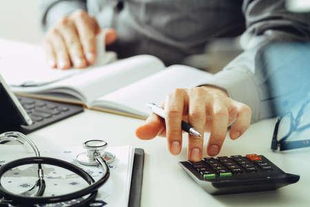 Concept de frais et honoraires de soins de santé. Main de docteur intelligent a utilisé une calculatrice pour les frais médicaux dans l'hôpital moderne Banque d'images - 83658302