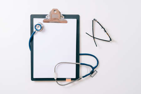 Blank stethoscope and gray clipboard and eyeglasses on white desk background Banque d'images