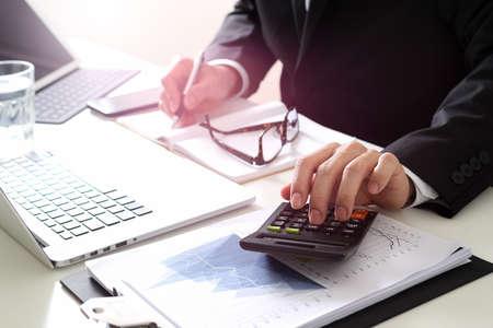 Zakenman hand werken met financiën over kosten en rekenmachine en laptop met mobiele telefoon op withe bureau in moderne kantoor