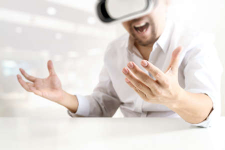technology: Businessman wearing virtual reality goggles in modern office with Smartphone using with VR headset