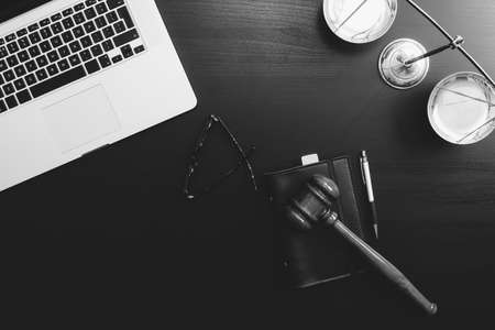 Justice and law concept.Lawyer workplace with laptop and documents with dark wooden,black and white Фото со стока