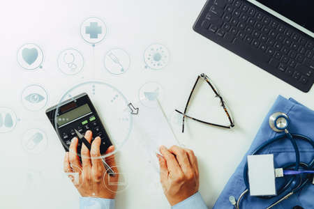 health care provider: Top view of Healthcare costs and fees concept.Hand of smart doctor used a calculator for medical costs in modern hospital with VR icon diagram Stock Photo