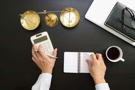 Rechtvaardigheid en wetsconcept zakenman of advocaat of accountant die aan rekeningen werken die een calculator en een laptop computer en documenten in modern bureau gebruiken