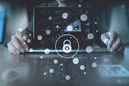 Cyber security internet and networking concept.Businessman hand working with VR screen padlock icon on computer background Banque d'images