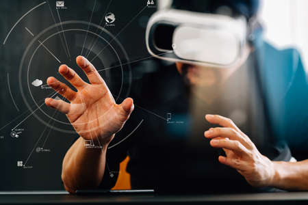 Businessman wearing virtual reality goggles in modern office with mobile phone using with VR headset with screen icon diagram