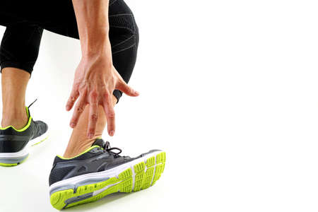 Runner sportsman holding ankle in pain with Broken twisted joint running sport injury and Athletic man touching foot due to sprain on white background Reklamní fotografie - 83658330