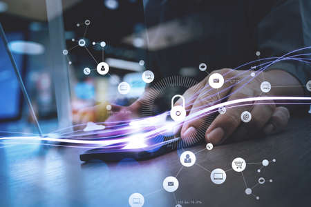 Cyber security internet and networking concept.Businessman hand working with VR screen padlock icon on mobile phone and laptop computer background
